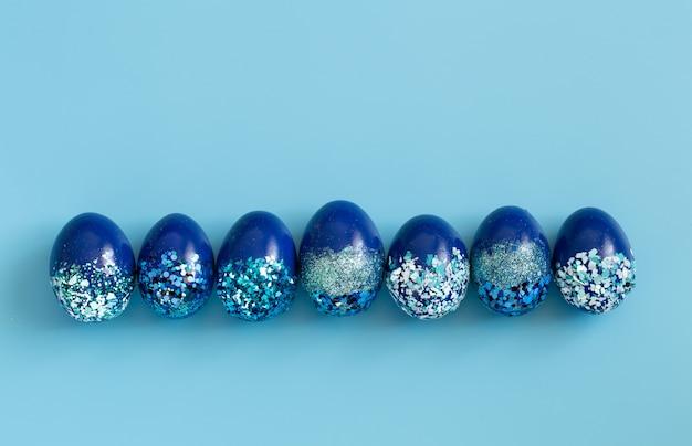 Piękna wielkanocna niebieska z niebieskimi ozdobnymi jajkami w cekinami.
