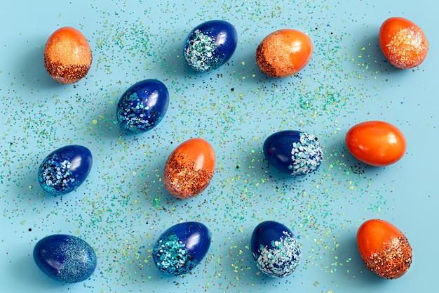 Piękna wielkanocna niebieska z niebiesko-pomarańczowymi ozdobnymi jajkami w cekinami.