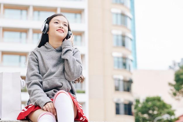 Piękna wietnamska nastolatka siedzi na zewnątrz i słucha dobrej muzyki w słuchawkach
