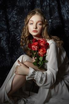 Piękna wiosna dziewczyna siedzi na podłodze z kwiatami róży w dłoniach. kobieta w białej sukni marzy, romantyczny wizerunek
