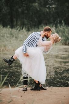 Piękna właśnie żonata namiętnie całuje się i obejmuje na wybrzeżu.