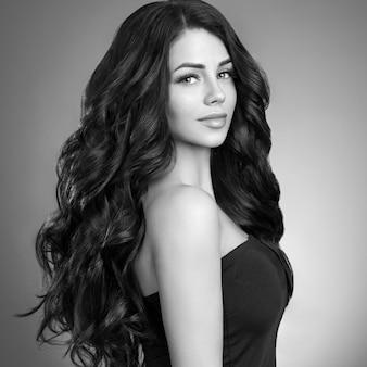 Piękna włosiana kobieta z długą brunetką fryzurą. strzał studio. monochromia. szary. czarny i biały.