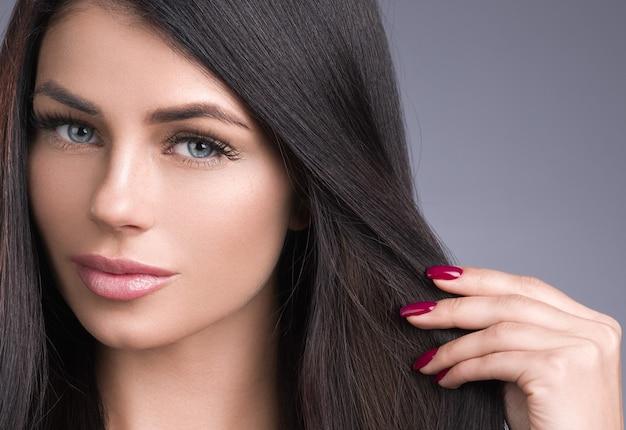 Piękna włosiana kobieta z długą brunetką fryzurą. strzał studio.