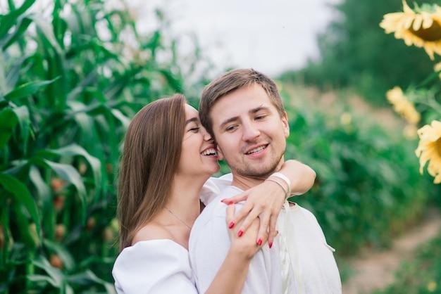 Piękna wspaniała kobieta i stylowy przystojny mężczyzna, rustykalna para całuje się w słonecznikowym polu, czule