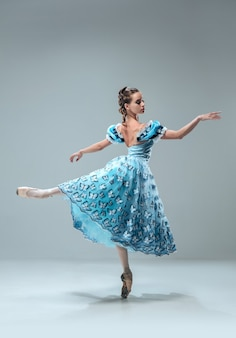 Piękna współczesna tancerka balowa na białym tle na szarym tle.