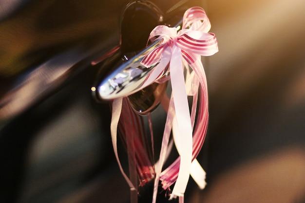 Piękna wstążka ozdobiona czarnymi klamkami do drzwi samochodu na ślub
