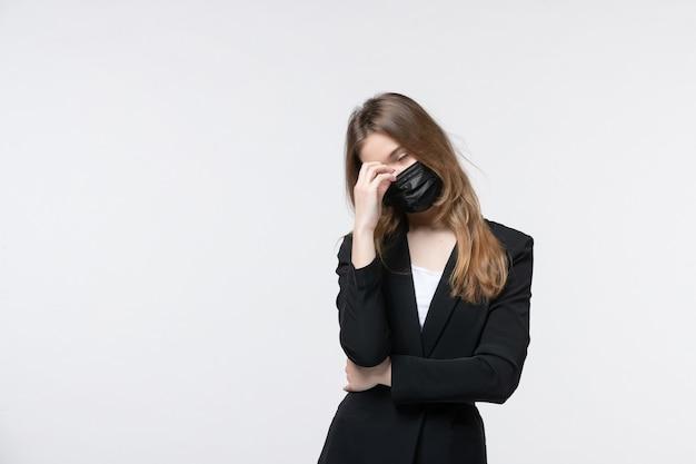 Piękna wyczerpana młoda dama w garniturze nosząca maskę chirurgiczną na białym