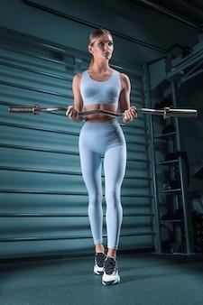 Piękna wysoka blondynka pozuje na siłowni ze sztangą w dłoniach na tle drążka. pojęcie sportu, fitness, aerobiku, kulturystyki, stretchingu. przedni widok.