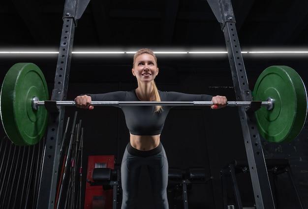 Piękna wysoka blondynka robi pompki z baru na siłowni. koncepcja fitness i kulturystyka. różne środki przekazu