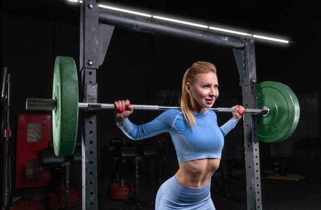 Piękna wysoka blondynka stoi na siłowni ze sztangą na ramionach. przysiady. koncepcja fitness i kulturystyka. różne środki przekazu