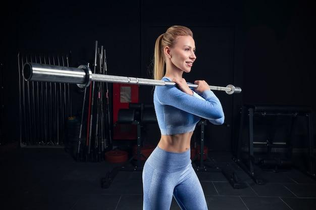 Piękna wysoka blondynka stoi na siłowni ze sztangą na ramionach. przysiady przednie. koncepcja fitness i kulturystyka. różne środki przekazu