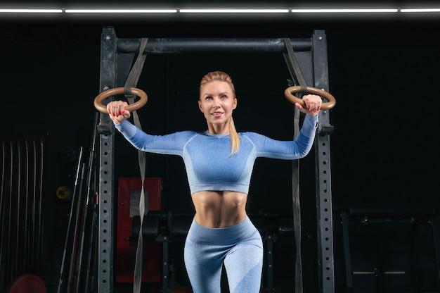 Piękna wysoka blondynka trenuje na atletycznych ringach. koncepcja fitness i kulturystyka. różne środki przekazu
