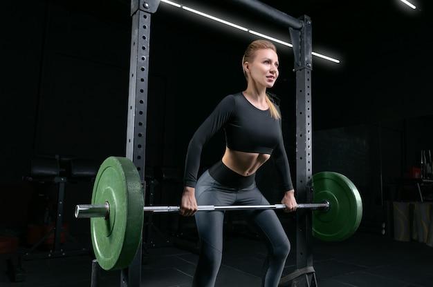 Piękna wysoka blondynka wykonuje ćwiczenie zwane martwym ciągiem. koncepcja fitness i kulturystyka. różne środki przekazu
