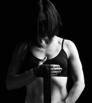Piękna wysportowana dziewczyna o czarnych włosach przewija rękę za pomocą czarnego elastycznego bandaża
