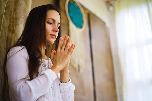 Piękna wysportowana dziewczyna robi ćwiczenia jogi cieszyć się medytacją w domu. bez stresu, zdrowy nawyk, koncepcja ulgi w lęku. pozycja lotosu.