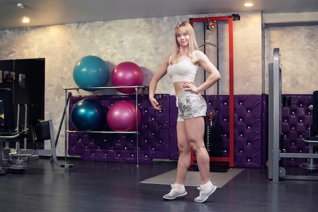 Piękna wysportowana kobieta pozuje na siłowni, blond kulturysta uśmiecha się i stoi w stojaku, aby pokazać swoje napompowane mięśnie