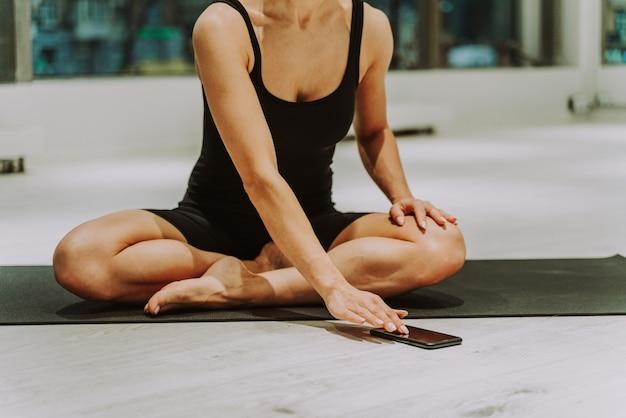 Piękna wysportowana kobieta trenuje na siłowni, robi ćwiczenia rozciągające przed treningiem