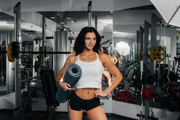 Piękna, wysportowana seksowna dziewczyna pozuje na siłowni po ciężkim treningu. fitness, kulturystyka.