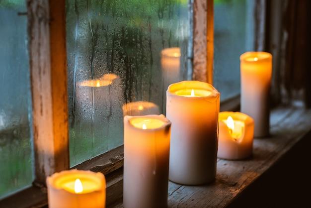 Piękna z kroplami deszczu na oknie i płonącymi świecami.