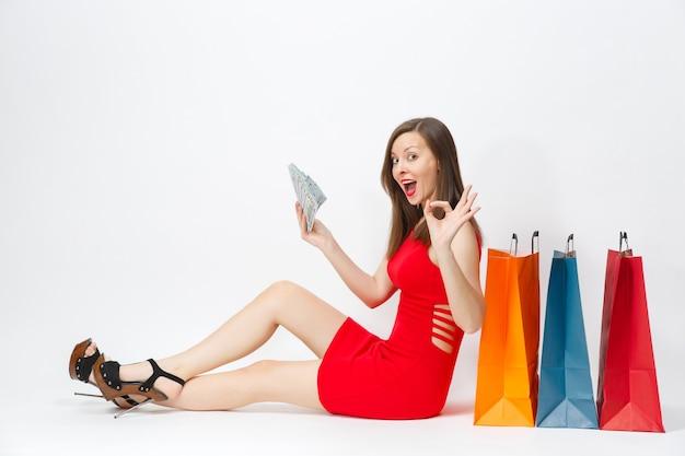Piękna zabawa glamour modna młoda kobieta w czerwonej sukience siedzi z dolarów gotówki, multi kolorowe pakiety z zakupami po zakupach na białym tle. skopiuj miejsce na reklamę.