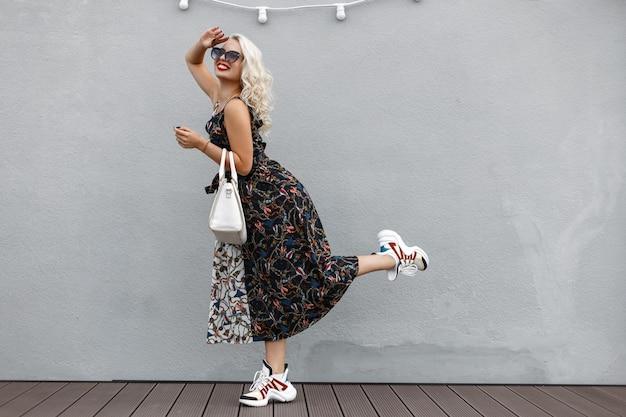 Piękna, zabawna, młoda, stylowa dziewczyna z modną białą torbą w sukience vintage pozuje w pobliżu szarej ściany