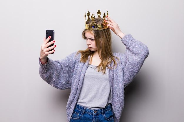 Piękna zabawna nastolatka z papierową koroną urodziny na kiju dokonywanie selfie z jej telefon komórkowy