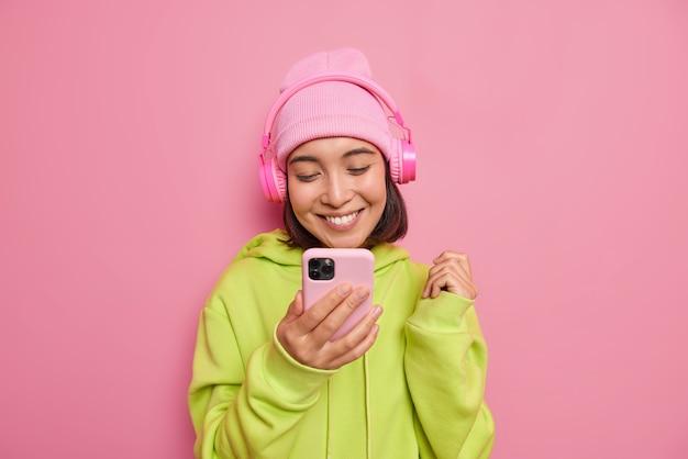 Piękna, zadowolona azjatycka nastolatka patrzy szczęśliwie na smartfona słucha muzyki przez słuchawki, cieszy się ulubioną playlistą, nosi kapelusz i zieloną bluzę na białym tle nad różową ścianą