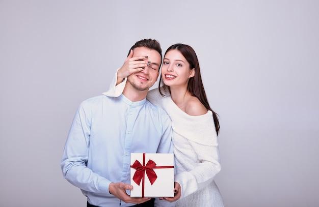 Piękna zakochana para daje prezenty, zamykając oczy na tle.