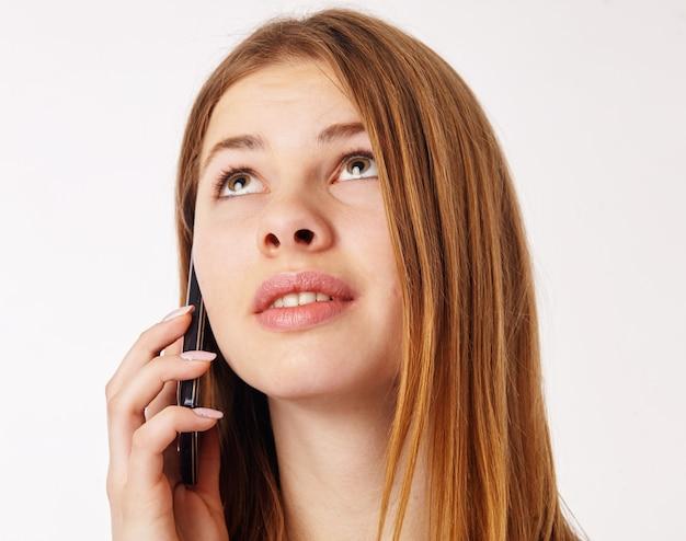 Piękna zamyślona kobieta rozmawia na smartfonie i patrzy w górę