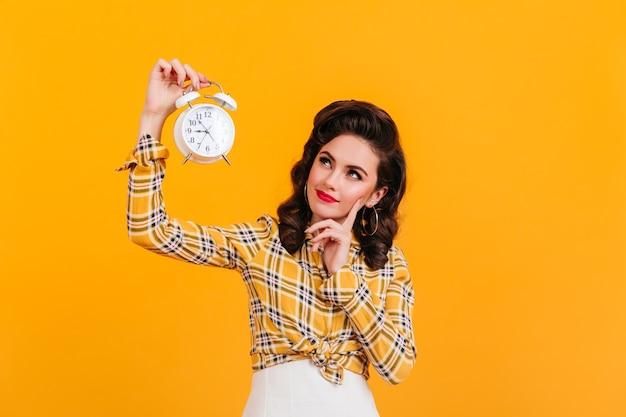 Piękna zamyślona kobieta trzyma zegar. strzał studio figlarny dziewczyna pinup stwarzających na żółtym tle.
