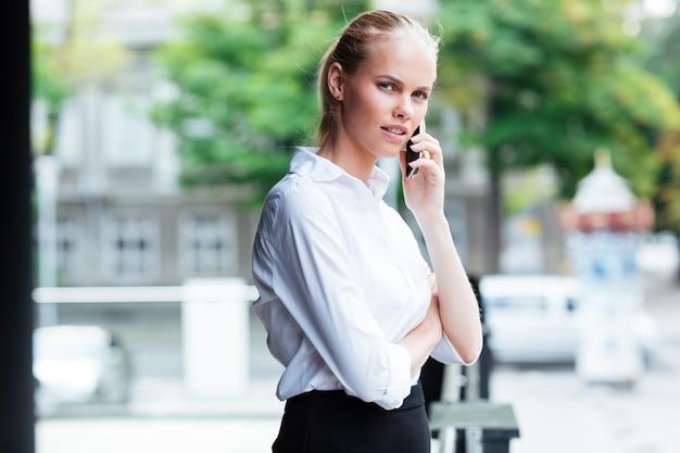 Piękna zamyślona młoda biznesowa kobieta rozmawia przez telefon komórkowy na zewnątrz