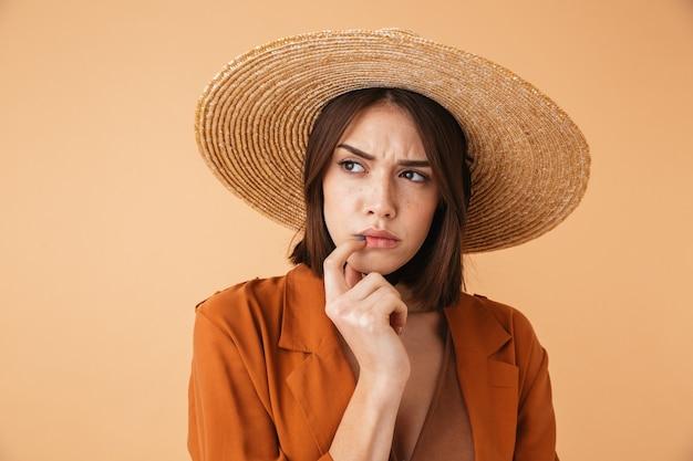 Piękna zamyślona młoda kobieta w słomkowym kapeluszu i letnim stroju stojąca na białym tle nad beżową ścianą