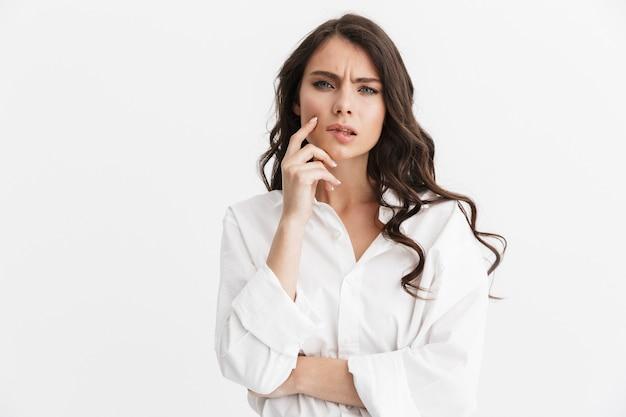 Piękna zamyślona młoda kobieta z długimi kręconymi włosami, ubrana w białą koszulę stojącą na białym tle nad białą ścianą