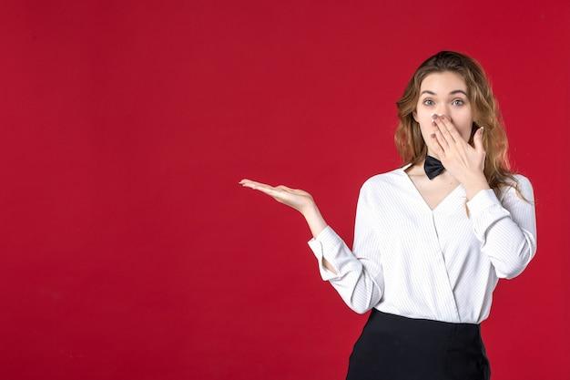 Piękna zaskoczona kelnerka motyl na szyi i wskazująca coś po prawej stronie na czerwonym tle