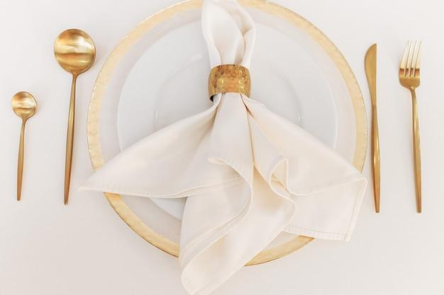 Piękna zastawa ślubna leży na białym stole. złote łyżki i widelce.