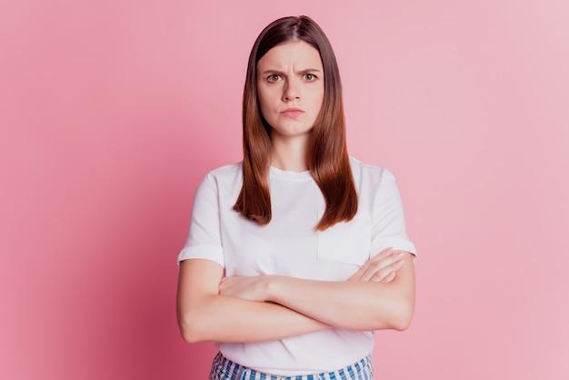Piękna zdenerwowana dziewczyna marszcząca urażoną twarz na białym tle na różowym tle
