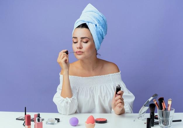 Piękna zdenerwowana dziewczyna owinięta ręcznikiem do włosów siedzi przy stole z narzędziami do makijażu, trzymając i nakładając błyszczyk, patrząc w dół na białym tle na fioletowej ścianie