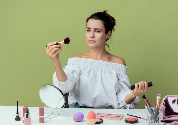 Piękna zdenerwowana dziewczyna siedzi przy stole z narzędziami do makijażu, trzymając pędzel i tusz do rzęs na białym tle na zielonej ścianie