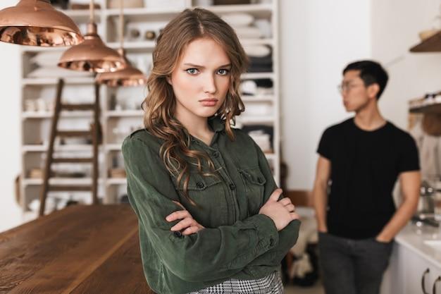 Piękna zdenerwowana kobieta z falowanymi włosami, trzymając ręce razem ze złością