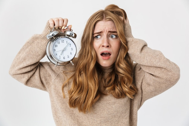 Piękna zdenerwowana młoda dziewczyna z długimi blond kręconymi włosami, ubrana w sweter, stojąca na białym tle nad białą ścianą, pokazująca budzik