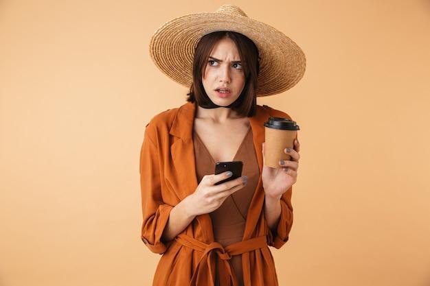 Piękna, zdenerwowana młoda kobieta w słomkowym kapeluszu i letnim stroju stojąca na białym tle nad beżową ścianą, trzymająca filiżankę kawy na wynos, używająca telefonu komórkowego