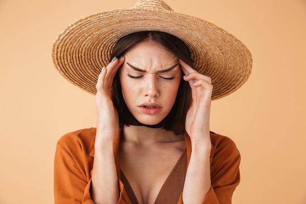 Piękna, zdenerwowana młoda kobieta w słomkowym kapeluszu stojąca na białym tle nad beżową ścianą, cierpiąca na ból głowy