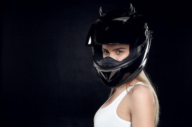Piękna, zdeterminowana młoda europejska motocyklistka ubrana w biały podkoszulek