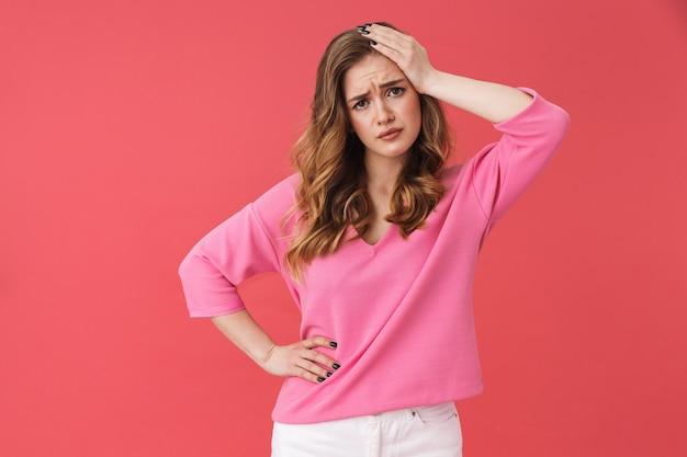 Piękna zdezorientowana młoda dziewczyna w zwykłych ubraniach, stojąca na białym tle nad różową ścianą, dotykająca głowy