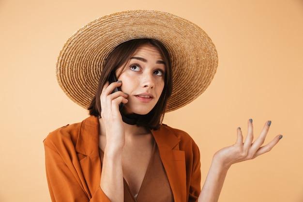 Piękna zdezorientowana młoda kobieta w słomkowym kapeluszu i letnim stroju stojąca na białym tle nad beżową ścianą