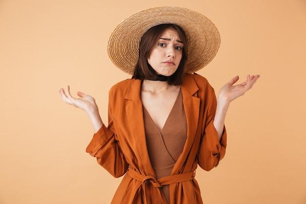 Piękna zdezorientowana młoda kobieta w słomkowym kapeluszu stojąca na białym tle nad beżową ścianą, wzruszając ramionami
