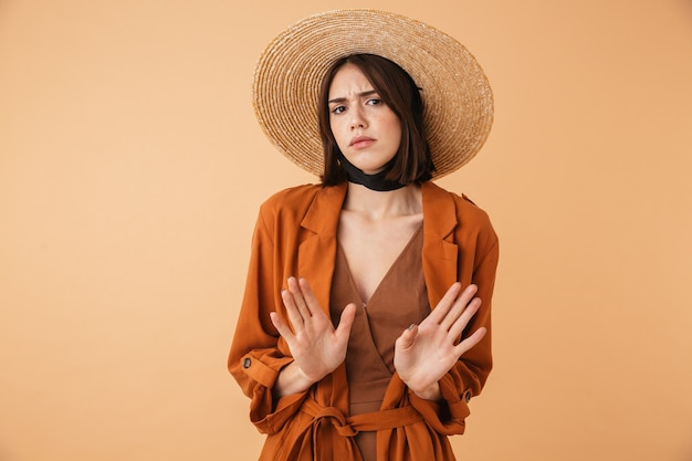 Piękna zdezorientowana młoda kobieta w słomkowym kapeluszu stojąca na białym tle nad beżową ścianą z wyciągniętymi ramionami