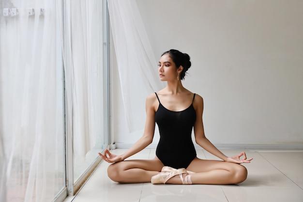 Piękna zdrowa azjatykcia kobieta cieszy się wewnątrz w balet sukni medytuje z joga pozą w domu z relaksem