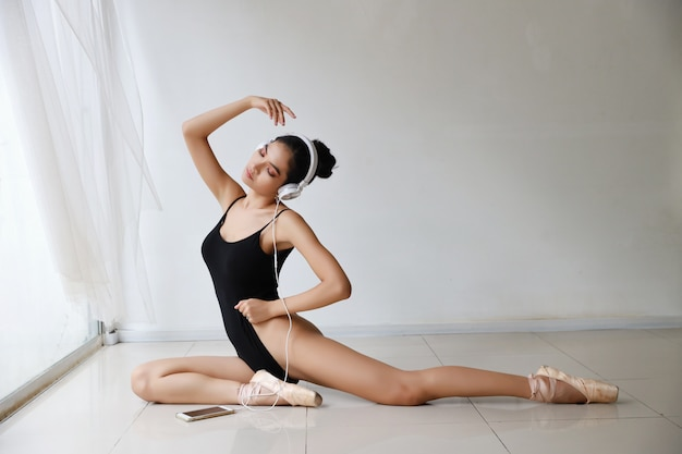 Piękna zdrowa i sportowa młoda azjatykcia kobieta w czarnym sportswear obsiadaniu z hełmofonem, słucha muzykę z telefonu komórkowego podczas gdy trenujący baleta tana na biel ścianie. technologia i zdrowy pojęcie