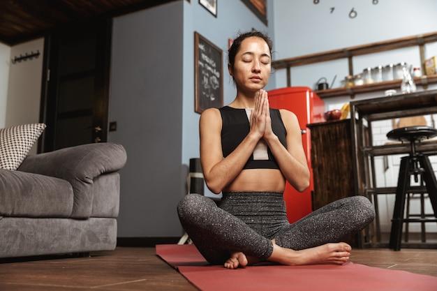 Piękna zdrowa kobieta robi ćwiczenia jogi, siedząc na macie fitness w domu